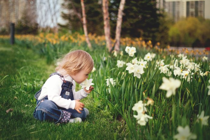girl-sitting-on-grass-smelling-white-petaled-flower