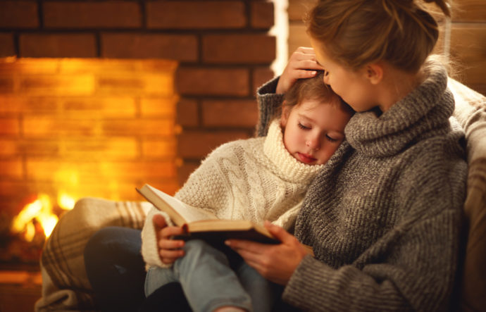 Mother reading a book to daughter - Family Ski Holiday