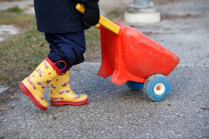 Toddler pushing wheelbarrow